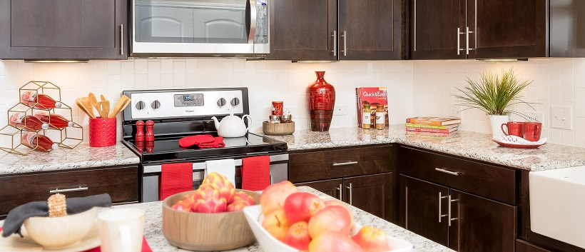 Kitchen with brown cabinetry, granite countertops and accents of red decor.