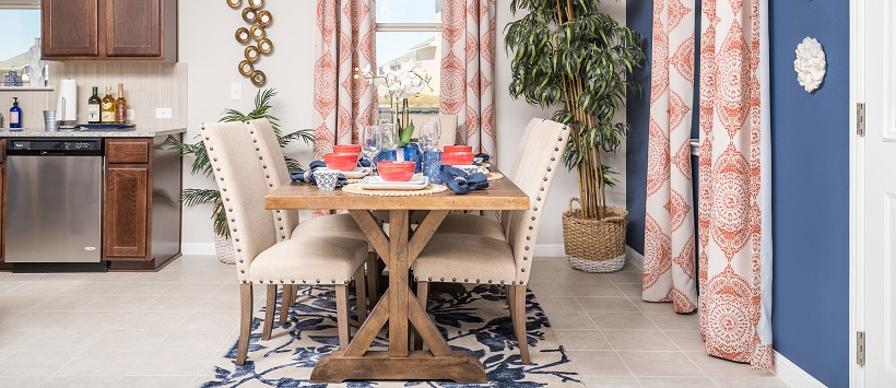 Dining room with a wooden table topped by red and blue china, next to a blue accent wall with red and white drapes.