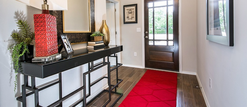 Entryway with thin red rug near a side table with a red lamp.