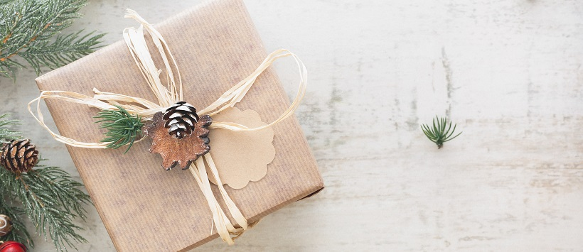 Brown paper package with straw ribbon and a pinecone ornament surrounded by Christmas tree needles.
