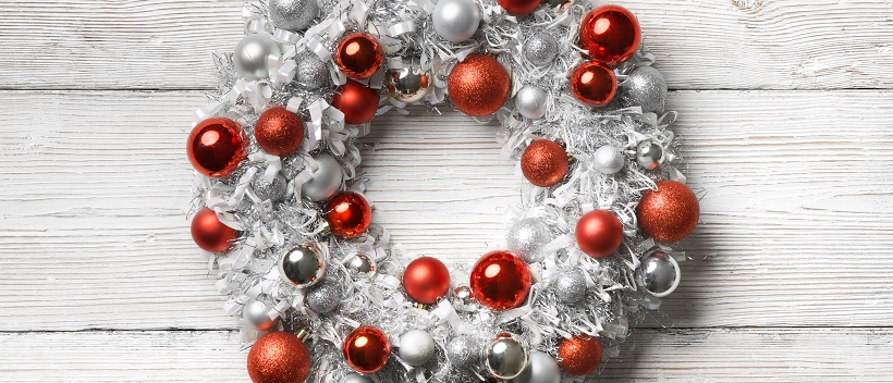 White wreath adorned with red and silver ornaments and placed on a white wooden background.