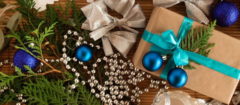 Christmas tree branches, silver beading, silver bows, and a brown package with a turquoise ribbon and blue ornaments.