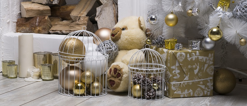 Under a white Christmas tree adorned with gold and silver ornaments, beige, white, and gold packages and decor sit with a wood pile in the background.