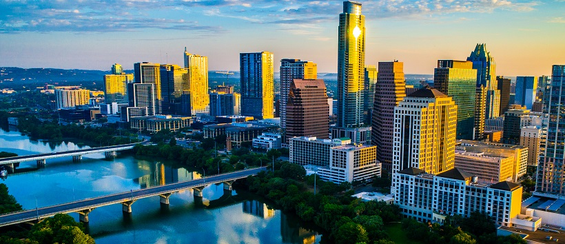 The sun casts a yellow hue over the skyrises in downtown Austin, Texas, and the fading blue sky is reflected in the clear, calm waters of Lady Bird Lake.