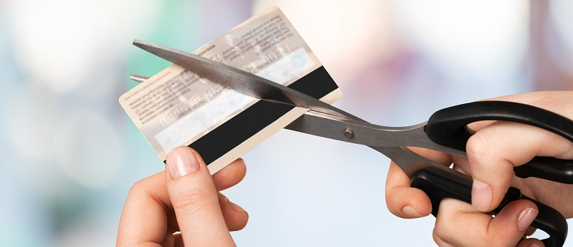 Person holding scissors and cutting credit card.