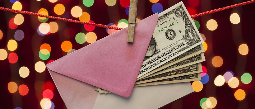 A string and clothespin is holding a pink envelope with dollar bills and Christmas lights in the background.