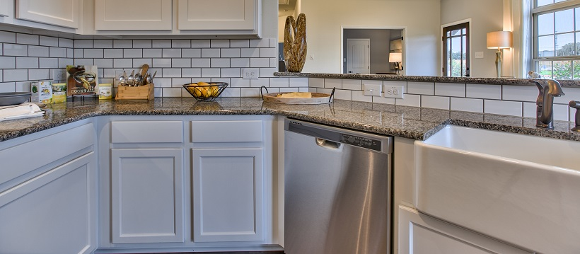 Kitchen with white cabinetry, granite, a stainless-steel dishwasher, and a deep farmhouse sink.