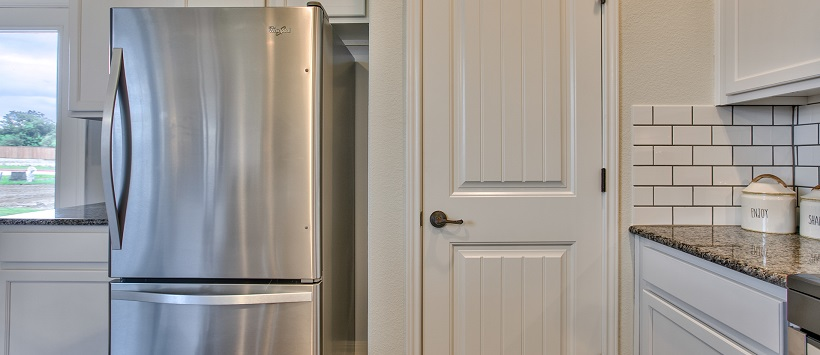 View of kitchen with stainless steel fridge next to a white pantry door.