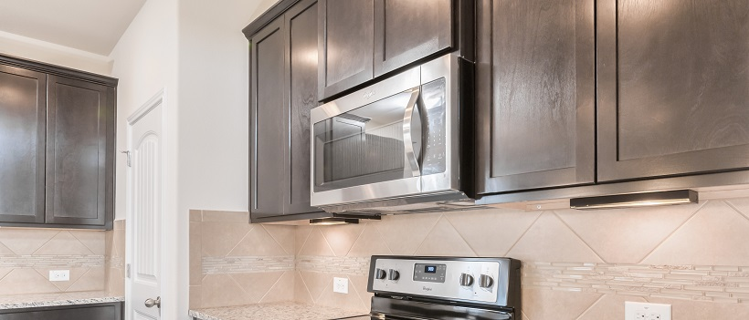 Kitchen view of a stainless steel microwave in between dark wooden cabinets and above a stove.