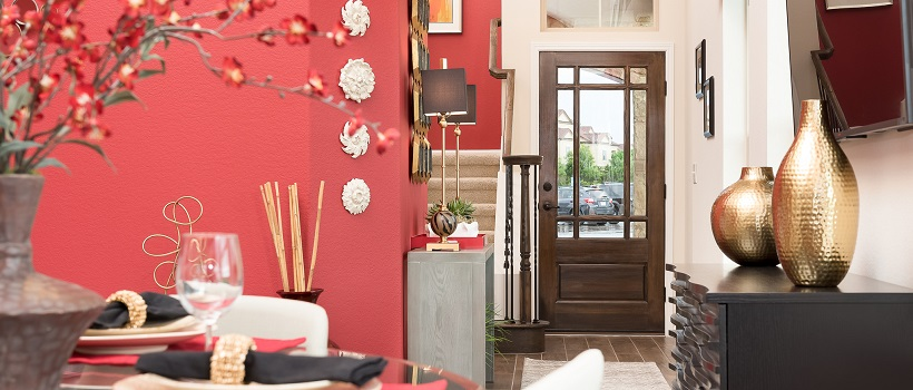 View from dining room of a vibrant salmon colored wall leading into an entryway and staircase.