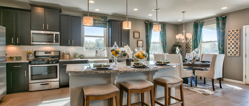 Near the dining area, a luxurious kitchen displays dark cabinetry, granite, and a large island with stools.