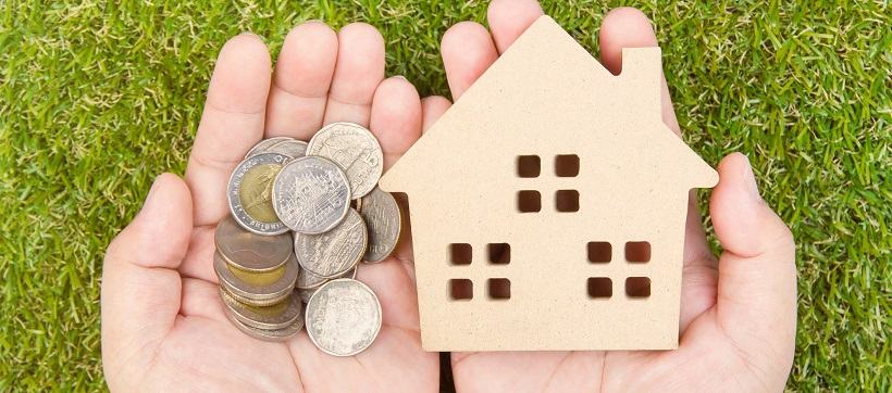 Hands holding coins and a mini wooden home with grass in the background.