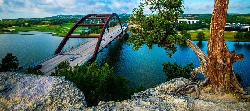 View of the Pennybacker Bridge stretching across the calm, blue waters of Lake Austin.