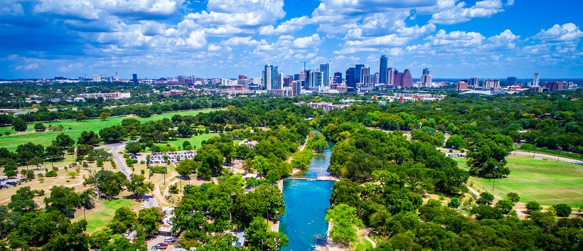 Beneath a blue sky filled with clouds, vibrant trees border a lake traveling towards downtown Austin in the distance.