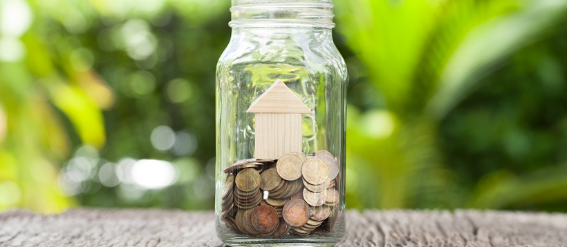 Outside, on a wooden table sits a glass jar with a wooden miniature home on top of coins.