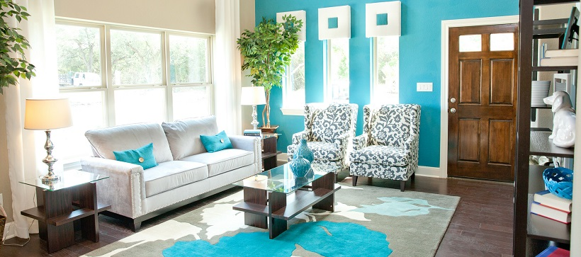 A vibrant living room with turquoise walls and white and turquoise furniture represents some of the best homes around Austin.