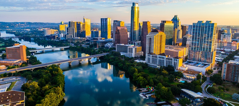 Sunset casts orange hues while creating blue shadows on the Austin cityscape with the Lady Bird Lake reflecting the sky above.