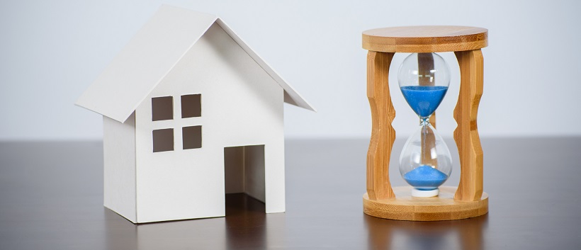 White miniature home next to an hourglass with blue sand.