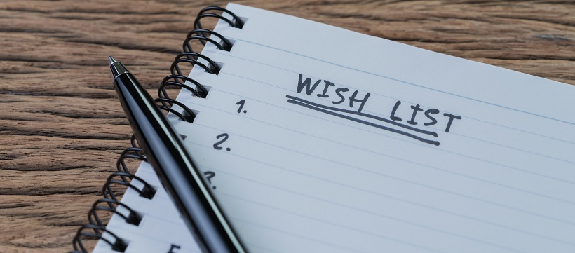 "Notepad with the words ""Wish List"" and numbers with pen sitting on top of paper."