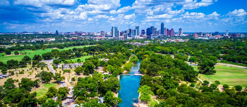 Skyline view of vibrant hill country and Lady Bird Lake leading towards downtown Austin, Texas.